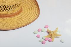Accessories for summer holidays. Straw hat on a white background. Near colored pebbles and starfish.  stock photo