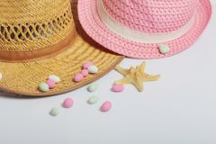 Accessories for summer holidays. Sun hats, colored pebbles and starfish on a white background.  royalty free stock images
