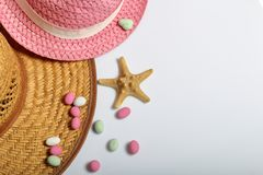 Accessories for summer holidays. Sun hats, colored pebbles and starfish on a white background.  royalty free stock photography