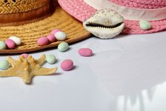 Accessories for summer holidays. Sun hats, seashells colored pebbles and starfish on a white background.  stock image