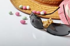 Accessories for summer holidays. Sun hats, sunglasses, colored pebbles and starfish on a white background.  stock photo