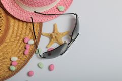 Accessories for summer holidays. Sun hats, sunglasses, colored pebbles and starfish on a white background.  stock images