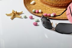 Accessories for summer holidays. Sun hats, sunglasses, colored pebbles and starfish on a white background.  royalty free stock photo