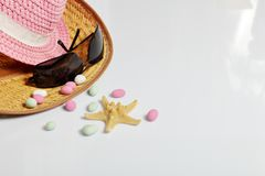 Accessories for summer holidays. Sun hats, sunglasses, colored pebbles and starfish on a white background.  royalty free stock images