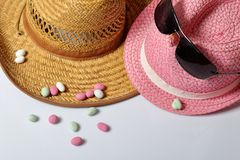 Accessories for summer holidays. Sun hats, sunglasses and colored pebbles on a white background.  royalty free stock photography