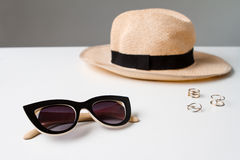 Accessories sunglasses and hat on white table. Stock Photos