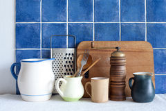 Accessories on the table. Stainless steel grater, green jug, vintage wooden spoons, cutting board. Stock Image