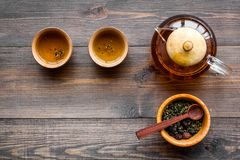 Accessories for tea ceremony. Tea pot, cups, dry tea leaves on dark wooden background top view copyspace Royalty Free Stock Images