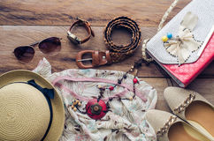 Accessories for teenage girl on her vacation, hat, stylish for summer sunglasses, leather bag, shoes and costume on wooden floor royalty free stock photography
