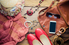 Accessories for teenage girl on her vacation. Straw hat, stylish sunglasses, brown leather bag, red shoes and costume on wooden fl Royalty Free Stock Photos