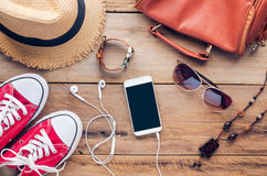 Accessories for teenage girl on her vacation. Straw hat, stylish sunglasses, brown leather bag, red shoes and costume on wooden Stock Photography