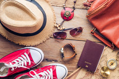Accessories for teenage girl on her vacation. Straw hat, stylish sunglasses, brown leather bag, red shoes and costume on wooden Royalty Free Stock Photo