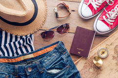 Accessories for teenage girl on her vacation. Straw hat, stylish sunglasses, brown leather bag, red shoes and costume on wooden Royalty Free Stock Images