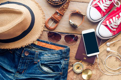 Accessories for teenage girl on her vacation. Straw hat, stylish sunglasses, brown leather bag, red shoes and costume on wooden Royalty Free Stock Image