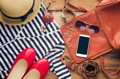 Accessories for teenage girl on her vacation. Straw hat, stylish sunglasses, brown leather bag, red shoes and costume on wooden Stock Photos