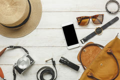 Accessories to travel with women clothing concept. Top view / Flat lay accessorize to travel and technology with woman / lady clothing on white wooden table Stock Image