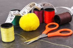 Accessories and tools for using in sewing. Spools of thread, needle, scissors and centimeter. Accessories and tools for using in sewing and needlework. Spools of stock photos