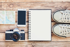 Accessories for travel. Passport, photo camera, smart phone and travel map. Top view. Holidays and tourism conceptt. Different objects on wooden background Royalty Free Stock Images