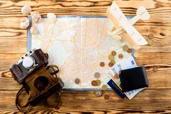 Accessories for travel. Retro vintage photo camera, travel map,. Passport, wallet with euro banknotes bills, seashells and wooden airplane, top view, flat Stock Photography