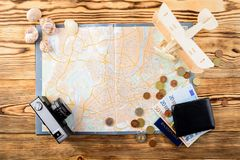 Accessories for travel. Retro vintage photo camera, travel map,. Passport, wallet with euro banknotes bills, seashells and wooden airplane, top view, flat Royalty Free Stock Photography