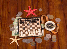 Accessories for  traveler: chess, compass and money on  dark wood. Royalty Free Stock Images