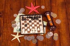 Accessories for  traveler: chess, hourglass money against dark wood. Stock Images