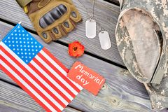 Accessories of US army veteran for memorial day. Glove, red poppy, dog tags and camouflage clothes. Top view, flat lay Stock Image