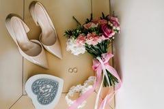 Accessorio di nozze Scarpe classiche, ` s della sposa del mazzo sulla tavola pastello Immagine Stock