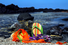 Accessorized at the Beach. Flip flops, scarf and colorful purple orchids lay on a pebbled beach on the Kohala Coast of the Big Island of Hawaii.  Pebbled beach Stock Images