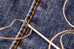 Accessory. Needle and thread on denim stock photo