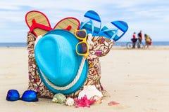 Accessory bag full sunbathers beach background Royalty Free Stock Photos