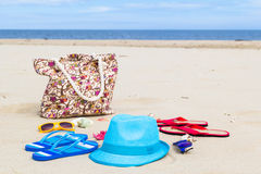 Accessory bag full sunbathers beach background Royalty Free Stock Photography