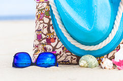 Accessory bag full sunbathers beach background Stock Images