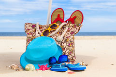 Accessory bag full sunbathers beach background Royalty Free Stock Image
