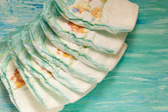 Accessory set for Baby disposable diapers on a turquoise background tree, items for baby care. Royalty Free Stock Photos
