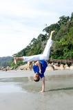 Acción acrobática del instructor del capoeira en la playa Fotos de archivo