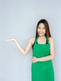 acción asiática de la muchacha con la habitación verde del delantal Fotos de archivo