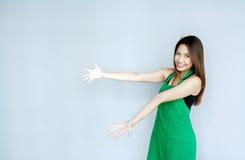 acción asiática de la muchacha con la habitación verde del delantal Foto de archivo