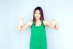 acción asiática de la muchacha con la habitación verde del delantal Imagenes de archivo
