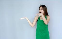 acción asiática de la muchacha con la habitación verde del delantal Fotos de archivo libres de regalías