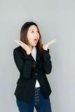 acción asiática de la sonrisa de la sorpresa de la muchacha con la habitación negra Fotos de archivo libres de regalías