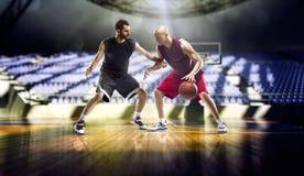 Acción de dos jugadores de básquet en el gimnasio Foto de archivo libre de regalías