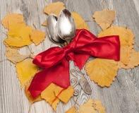 Acción de gracias en el otoño, consistiendo en los cubiertos y la ubicación de hojas y de cuerdas que caen en un fondo de madera  Fotografía de archivo libre de regalías