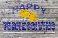 Acción de gracias feliz azul en fondo de madera con dos hojas amarillas Fotografía de archivo