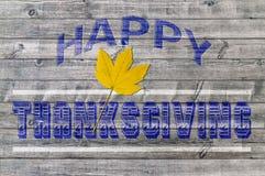 Acción de gracias feliz azul en fondo de madera con la hoja amarilla Fotografía de archivo libre de regalías