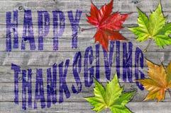 Acción de gracias feliz azul escrita en el tablero de madera y las hojas coloridas Foto de archivo