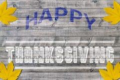 Acción de gracias feliz azul y blanca en fondo de madera con la hoja amarilla cuatro Fotos de archivo