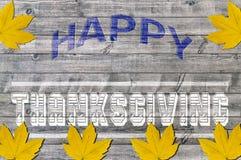 Acción de gracias feliz azul y blanca en fondo de madera con varias hojas amarillas Fotos de archivo