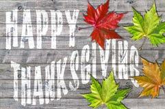 Acción de gracias feliz blanca escrita en el tablero de madera y las hojas coloridas Imagenes de archivo