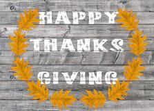 Acción de gracias feliz blanca escrita en fondo del tablero de madera con las hojas amarillas Imagenes de archivo